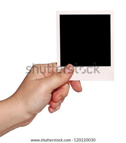 Isolated close-up shot of a human hand holding instant photo. - stock photo
