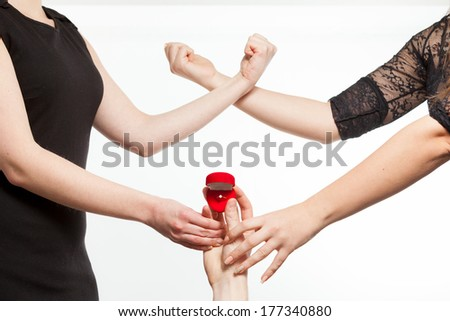 Isolated closeup photo of two jealousy girls fighting for a ring being held by man  - stock photo