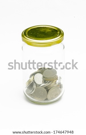 Isolated coins in glass jar - saving concept - stock photo