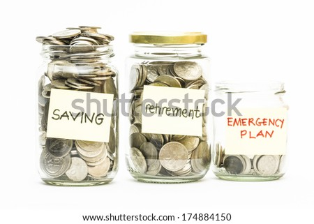 Isolated coins in jar with saving, retirement and emergency plan label - financial concept