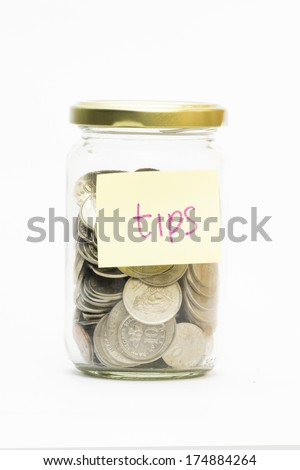 Isolated coins in jar with tips label - financial or business concept - stock photo