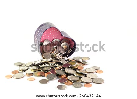 Isolated coins spilling from a heart box - stock photo