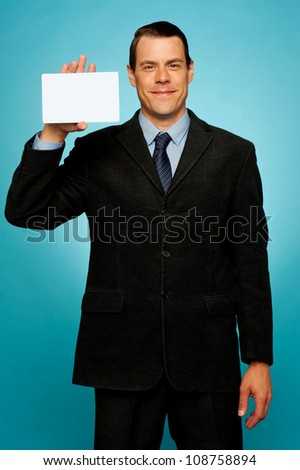 Isolated corporate man holding blank placard, showing it to camera - stock photo