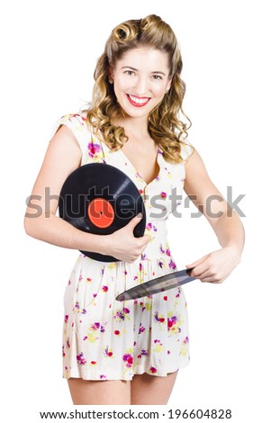 Isolated disco pinup girl with pretty hair style and makeup rocking out to LPs at a retro party from 1950 when spinning records. DJ pin-ups