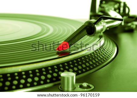 Isolated DJ turntable vinyl records player for party,concert,night club event.Close up,focus on turntables needle over record.Audio equipment for professional disc jockey.Green color