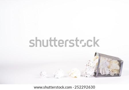 isolated fallen wastebasket full of white waste paper - stock photo