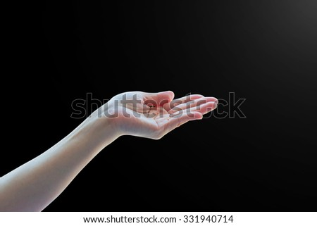 Isolated female empty open woman hand with palm raised upward in black and white dark color tone with rim light: Pray for help, hope, spiritual support: Humanitarian aid and human rights concept