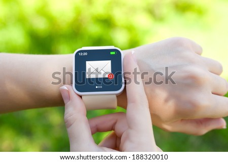 Isolated female hands with white smartwatch with email on the screen on a background of green grass - stock photo