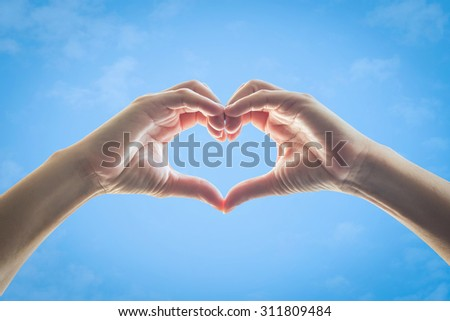 Isolated female human hands in heart shape raising against clear bright blue sky background: Universal hand sign language expression meaning love, caring, friendship, trust, hope, healthy life, peace