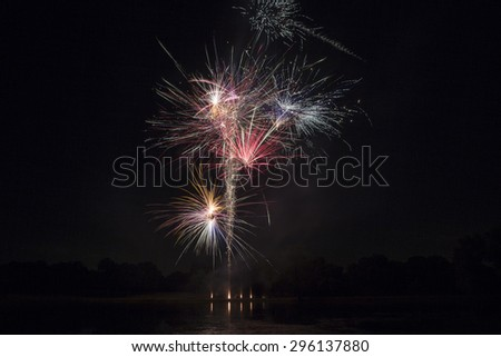 Isolated fireworks with slight lake water reflection