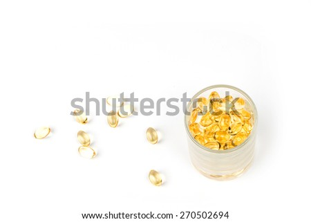 Isolated fish oil capsules in glass isolated on white background - stock photo
