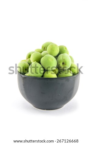 Isolated fruit : fresh green ume (Japanese plums) in the black ceramic bowl. - stock photo