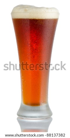 Isolated full length portrait of a full cold beer in pilsner style glass with head above rim level and partial reflection - stock photo