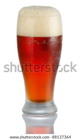 Isolated full length portrait of a full cold beer in tumbler style glass with large head above rim level and partial reflection