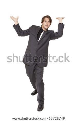 Isolated full length studio shot of a businessman looking at the camera while posed as if he were supporting a large weight over his head. - stock photo