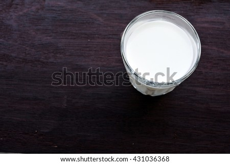 Isolated glass of milk on wooden table - stock photo