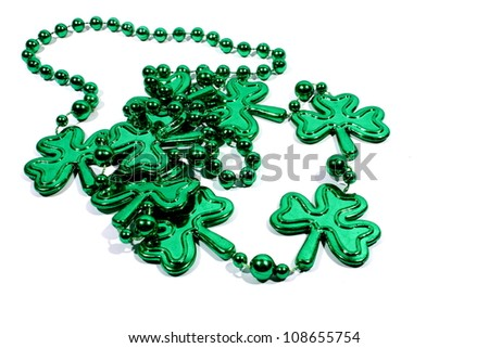 Isolated green mardi gras necklace with three leaf clovers. - stock photo