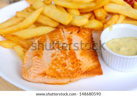 isolated grilled salmon in white plate with fries and cream sauce