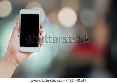 isolated hand holding mobile phone with clipping path, woman hand holding mobile, smart phone with black blank screen for copy text space on colorful bokeh background : Technology mobile phone concept