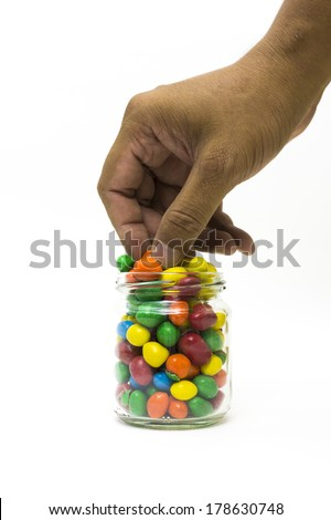 Isolated hand pick a candy on white background. - stock photo