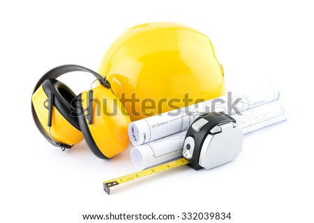 isolated hard hat with plans and measuring tape and hearing protection ear muffs on white