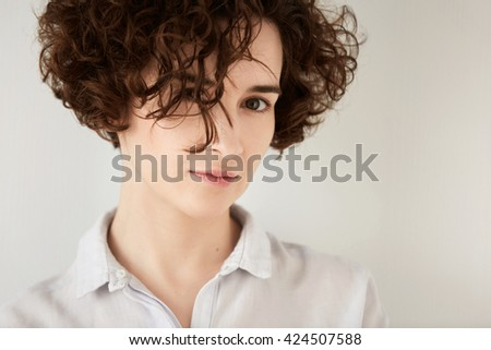 Isolated headshot of beautiful hipster girl with short curly hair wearing white trendy shirt looking at the camera. Portrait of young female with messy hairstyle relaxing at home. Lifestyle concept - stock photo
