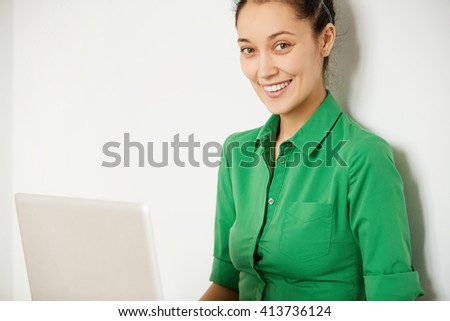 Isolated headshot of happy female in green shirt looking with cute smile at the camera. Cropped view of successful young businesswoman smiling while working on laptop in the office. Selective focus - stock photo