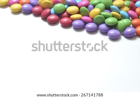 Isolated heap of colored smarties on white background shape like upper frame - stock photo