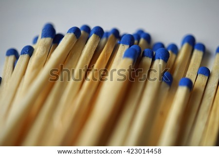 Isolated heap of safety match sticks made of small blue heads and short wooden prisms  - stock photo