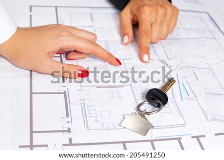 Isolated house key on top of house project. - stock photo