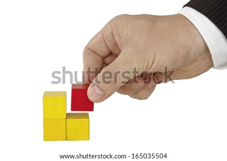 Isolated human hand finishing four blocks yellow - stock photo