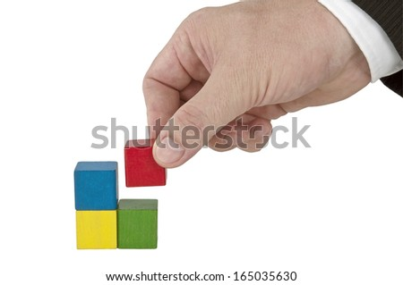 Isolated human hand finishing four color blocks - stock photo