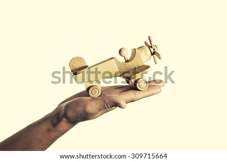 isolated image of a hand with an open palm on which the handmade wooden aircraft - stock photo