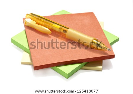 Isolated image of a pile of sticky note in assorted colors with a pen on top against a white background