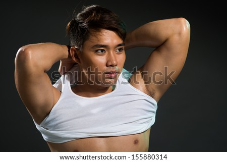 Isolated image of a sexy man putting off the clothes over black