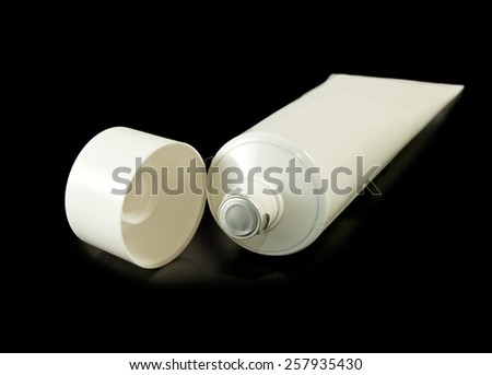 Isolated image of a tube of toothpaste on a black background  - stock photo