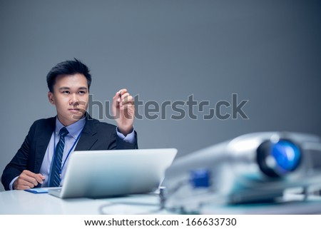 Isolated image of a young concentrated businessman pointing at something with the pen while working on the foreground  - stock photo
