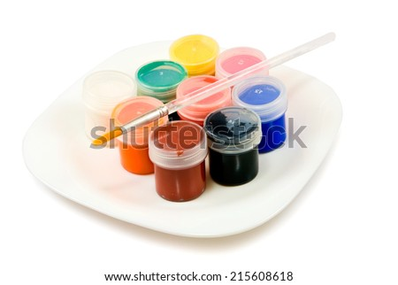 Isolated image of different paints and brush on a white plate closeup - stock photo