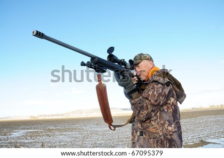 Isolated image of hunter with rifle.  Image took place in Wyoming while hunting big-game. - stock photo
