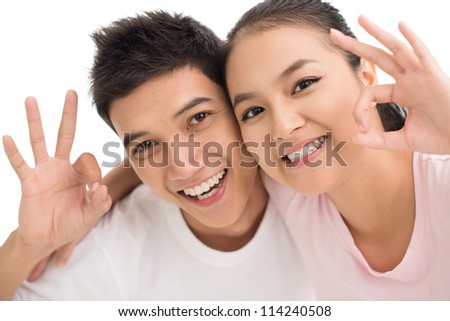 Isolated image of two young people doing an ok sign - stock photo
