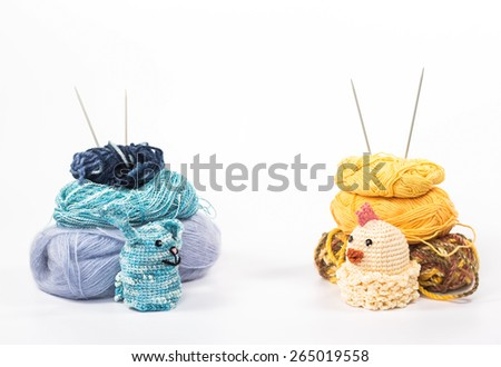 isolated knitting toy chicken and rabbit on a background of skeins - stock photo