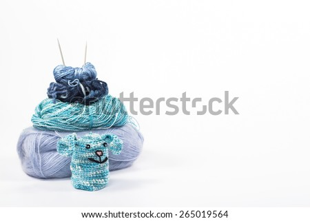 isolated knitting toy rabbit on a background of skeins - stock photo