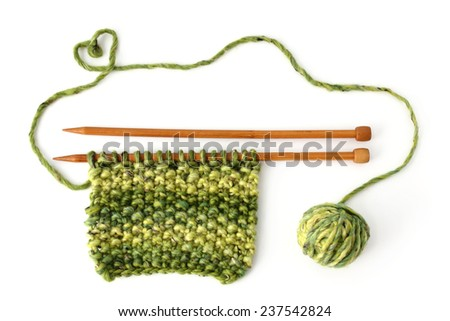 Isolated knitting with green wool - stock photo