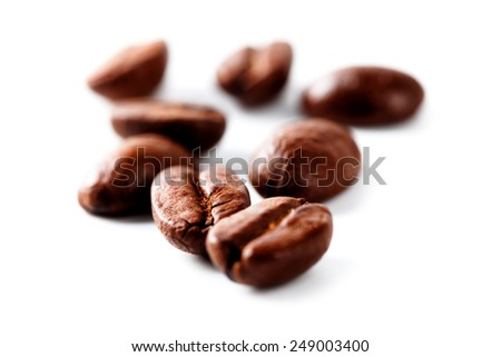 isolated macro shot of coffee beans on white background - stock photo