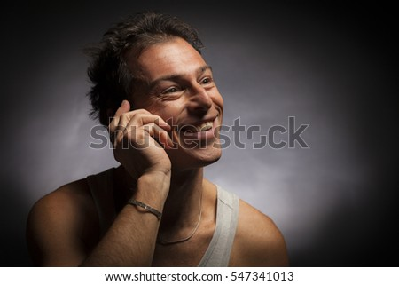 Isolated man talking on the mobile phone. Black background