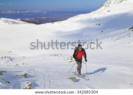 Isolated mountaineer traversing a white slope on the mountain in winter  - stock photo