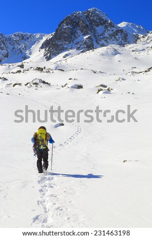 Isolated mountaineer walking on a snow field in winter