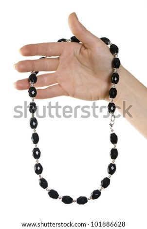 Isolated necklace of black stones in hand