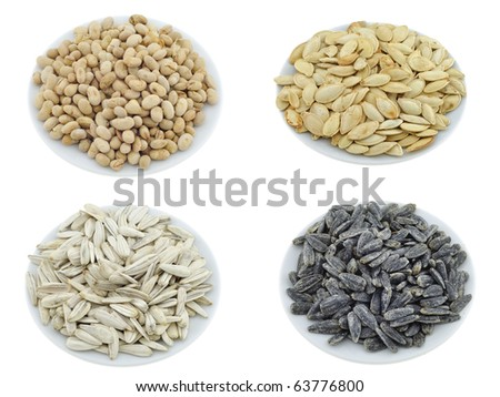 Isolated nuts, seeds and appetizers on white plate - stock photo