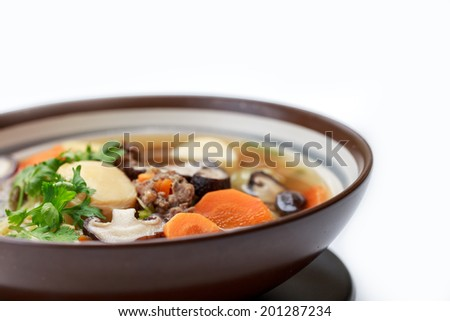 Isolated of Thai and asian style mushroom soup are mildly seasoned soup that Consisting of pork, tofu, carrots, Chinese Cabbage and mushrooms. Usually eaten with rice. good for children and the sick